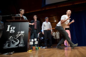 Bruno Grossi (R), walks like a dinosaur as he and his team accept the Ig Nobel Prize in Biology for observing that when you attach a weighted stick to the rear end of a chicken, it then walks in a manner similar to that in which dinosaurs are thought to have walked, at the 25th First Annual Ig Nobel Prizes awards ceremony at Harvard University in Cambridge, Massachusetts September 17, 2015. The annual prizes, meant to entertain and encourage global research and innovation, are awarded by the Annals of Improbable Research as a whimsical counterpoint to the Nobel Prizes. REUTERS/Gretchen Ertl - RTS1NKR