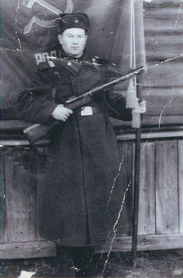 Боец Петр Конкин на фоне знамени полка